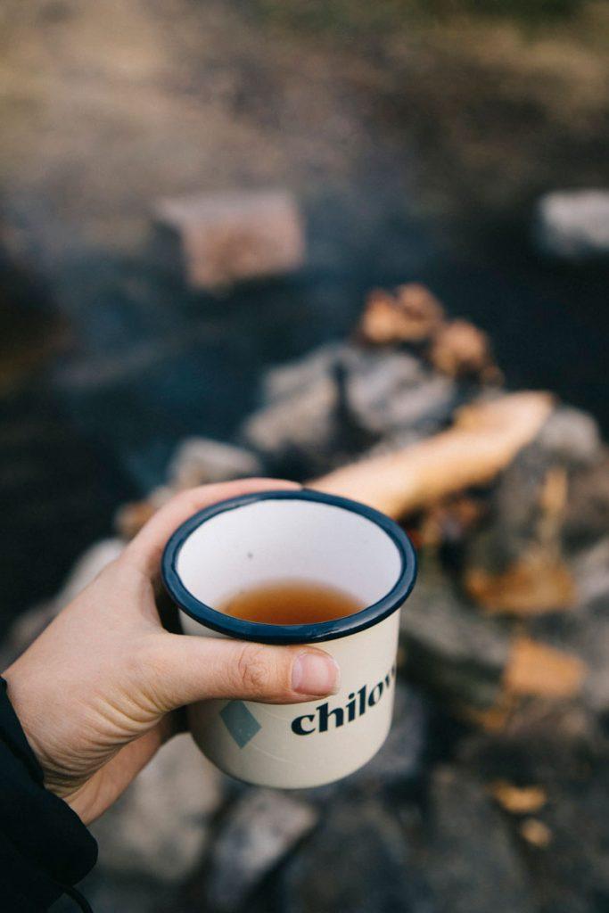 partager une tasse de thé avec d'autres randonneurs au coin du feu