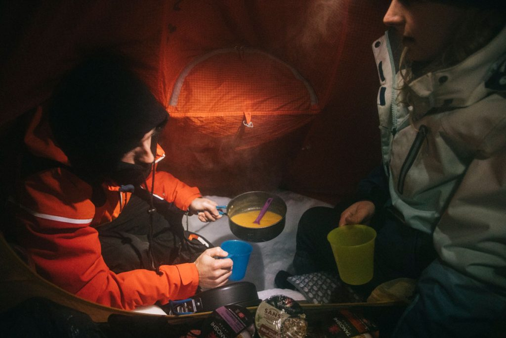 Faire à manger dans la tente lors d'un bivouac en hiver. crédit photo : Clara Ferrand - blog Wildroad